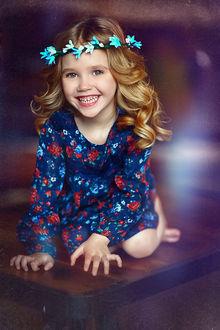 Фото Девочка маленькая красивая голубоглазая с венком и колокольчиков на голове, радостно улыбаясь, сидит на столе. Фотограф Наталья Законова