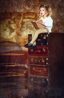 Фото Маленькая красивая девочка с удивленным взглядом сидит на этажерке с чемоданами, держа книгу в руках. Фотограф Наталья Законова