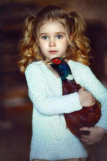 Фото Девочка голубоглазая красивая с удивленным в взглядом с хвостиками держит в руках птицу, фотограф Наталья Законова