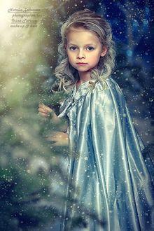 Фото Девочка маленькая белокурая, голубоглазая в легком атласном плаще на зимнем фоне, фотограф Наталья Законова