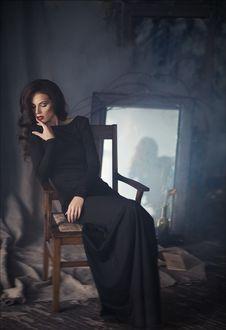 Фото Девушка в черном платье сидит на стуле, позади видно ее отражение в запыленном зеркале, фотограф Алина Троева