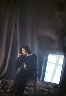 Фото Девушка в черном платье сидит на стуле, позади нее стоит запыленное зеркало, фотограф Алина Троева