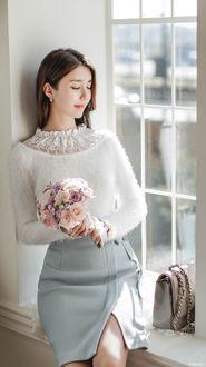 Фото Девушка азиатской внешности в белой кофте и серой юбке с букетом цветов в руках сидит на подоконнике