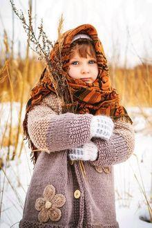 Фото Девочка в снегу закутанная в палантин с ветками в руках