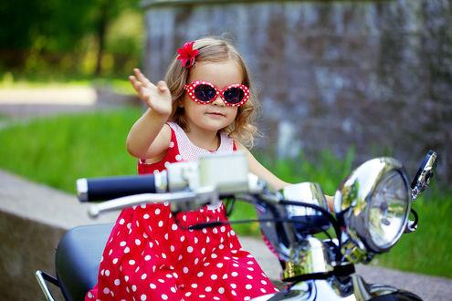 Фото Девочка на мотоцыкле в красных очках и платье в белый горошек