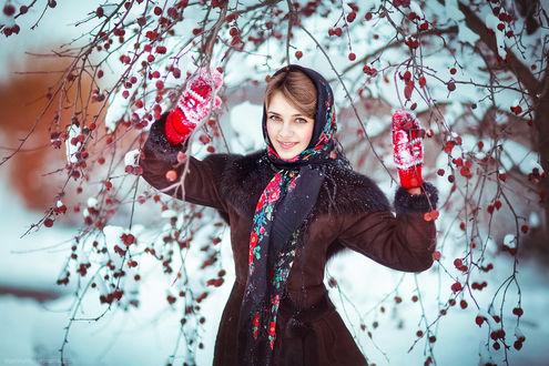 Фото Девушка в зимней одежде подняла вверх руки в красных варежках к веткам с красными плодами, усыпанных снегом, by olgaboyko