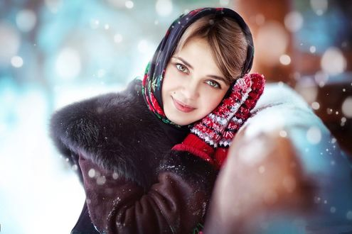 Фото Девушка положила голову на руки в красных варежках, прислонившись к покрытым снегом перилам