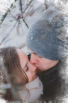 Фото Парень целует девушку на фоне зимнего пейзажа