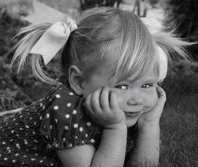 Фото Девочка с бантиками лежит на траве