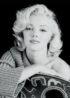 Фото Звезда Голливуда прекрасная Marilyn Monroe в вязаной кофте облокотилась на какой-то предмет, похожий стул