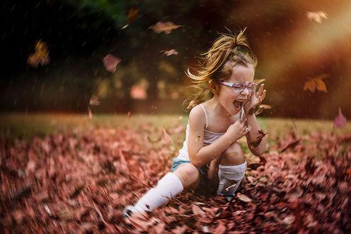 Фото Девочка с закрытыми глазами в очках сидит на осенней листве, которая вихрем кружит вокруг нее