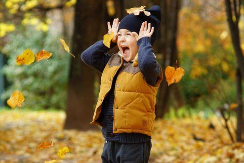 Фото Мальчик с поднятыми руками на фоне падающих осенних листьев, фотограф Михаил Пелид