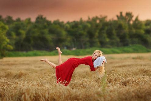 Фото Девушка в красном платье и подушкой в руках летает над колосящимся полем и машет ножками, фотограф Максим Матвеев
