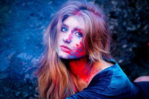 Фото Красивая девушка с голубыми глазами и разводами краски на лице