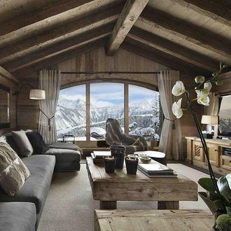 Фото Комната в деревянной доме, вид из окна которой открывается на заснеженные горы
