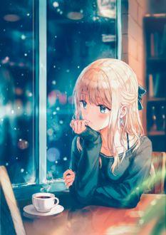 Фото Девочка сидит за столиком с чашкой кофе