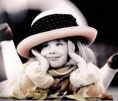 Фото Милая девочка в шляпке лежит и игриво болтает ножками