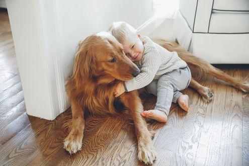 Фото Маленький мальчик обнимает собаку