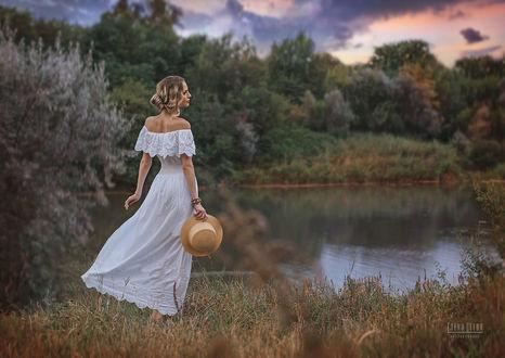 Фото Девушка со шляпой в руке стоит на фоне водоема, фотограф Елена Деева
