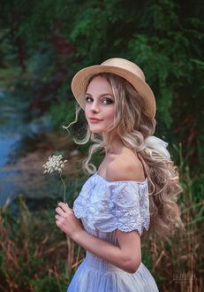 Фото Девушка в шляпке и цветком в руке стоит на фоне природы, фотограф Елена Деева
