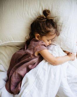Фото Девочка в платье спит, обняв ручками одеяло