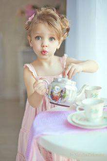 Фото Маленькая хозяюшка. Девочка в розовом платьице разливает чай по чашкам