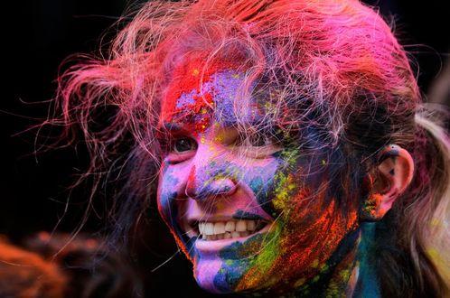 Фото Девушка смеется, а ее лицо разрисовано цветными красками, Фестиваль Холи, фестиваль цветов, весны в Индии