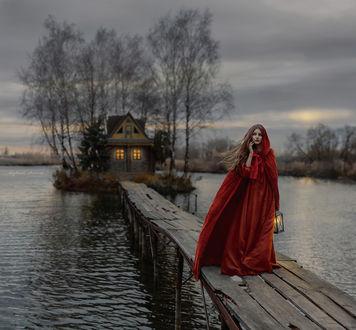 Фото Девушка в длинной красной одежде с капюшоном, с фонарем в руке стоит на мостике, фотограф Ирина Джуль