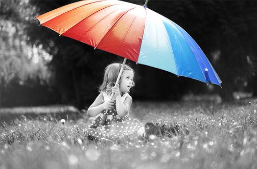 Фото Девочка сидит на траве под цветным зонтом