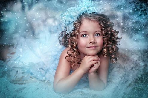 Фото Девочка - ангел на фоне снега, сложила руки у лица, на голове снежный бант, фотограф Наталья Родионова