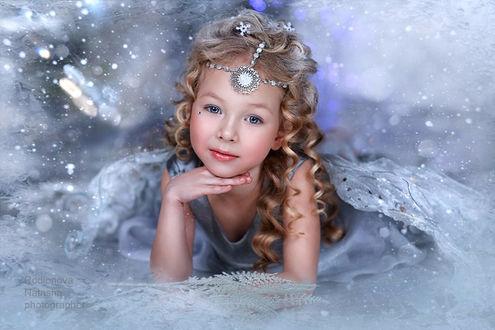 Фото Девочка снежный ангел лежит в прозрачном платье, на голове украшение из медальона, на фоне бликов снега, фотограф Наталья Родионова