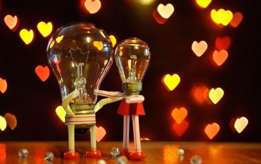 Фото Две лампочки обнимают друг друга, олицетворяя влюбленную пару, а вокруг падают сердечки