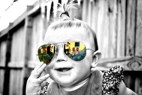 Фото Девочка придерживает цветные очки, в которых отражаются люди и дома