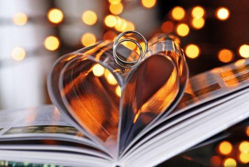 Фото Два обручальных кольца лежат на книжных страницах, согнутых в виде сердца