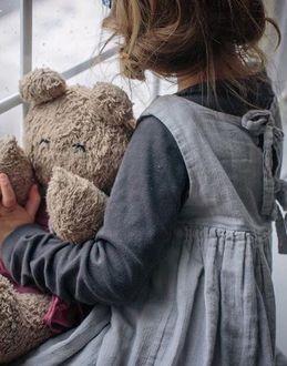 Фото Девочка с игрушкой в руках стоит у окна