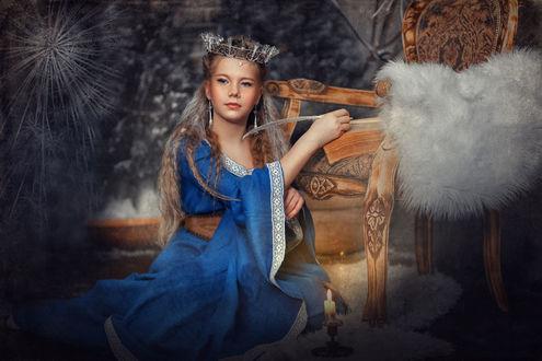 Фото Девушка с золотыми волосами, ажурной короной на голове, держит в руке перо, собираясь писать в большой книге на стуле, рядом горит свеча
