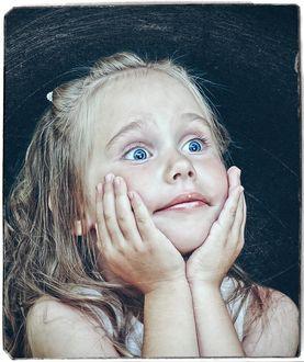 Фото Удивленная девочка держит руки у лица