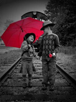 Фото Дети стоят на железнодорожном полотне, взявшись за руки, девочка с красным зонтом, а мальчик с красным цветком, позади них паровоз
