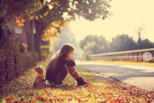 Фото Девочка с игрушечным мишкой сидят на траве с листвой у дороги