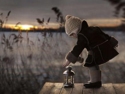 Фото Девочка в тулупчике поставила на речной мосточек фонарик