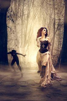 Фото Девушка готесса на фоне леса с кулоном на шее в виде перевернутых весов, за ней томится позади у дерева злой дъявол, by Peter Brownz Braunschmid