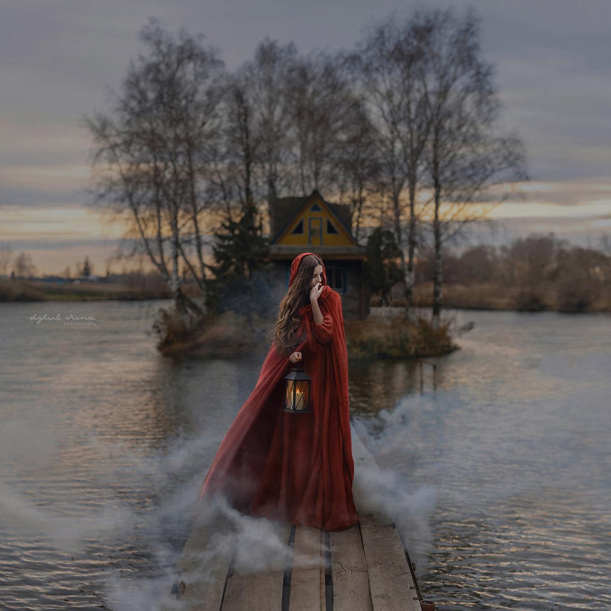 Фото Девушка в красном плаще с фонарем в руке стоит на мостике, ведущем к небольшому островку, фотограф Ирина Джуль
