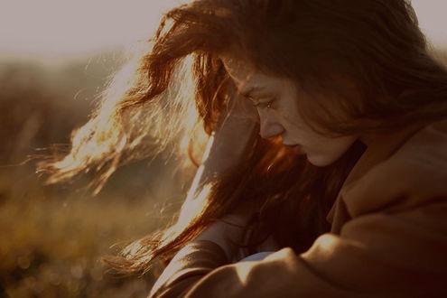 Фото Грустная девушка, с рыжими развевающимися волосами, опустив глаза смотрит вниз, by M0THart