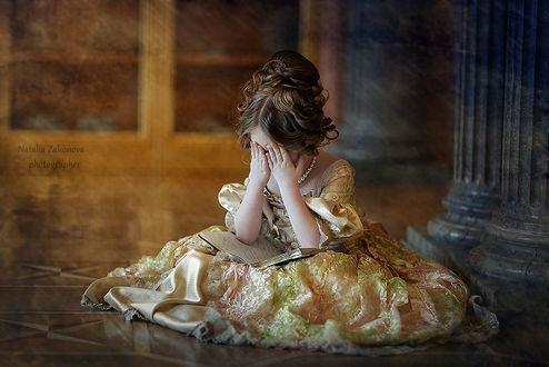 Фото Маленькая девочка грустная c высокой прической, в пышном платье сидит на полу держа на коленях книгу, закрыла руками лицо, на фоне старинного помещения. Фотограф Наталья Законова / Natalia Zakonova