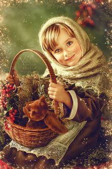 Фото Девочка, улыбающаяся с красивыми большими глазами, в теплом вязанном полушалке и в фартуке, слегка запорошена снегом, держит на коленях корзинку, в которой лежат грозди ягод и любимая игрушка медвежонок. Фотограф Карина Киль / Karina Kiel