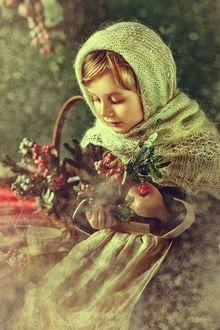 Фото Девочка в вязанном полушалке и фартуке держит в руках еловые ветки и ветки с ягодами, смотря на них, на размытом фоне, где стоит корзина с дарами природы и чашка с блюдцем. Фотограф Карина Киль / Karina Kiel