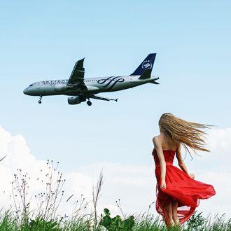 Фото Девушка в красном платье смотрит на летящий самолет