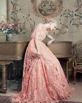 Фото Девушка в нежно розовом ажурном длинном платье в грусти облокотилась на рояль