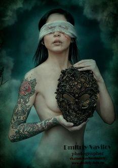Фото Обнаженная девушка с повязкой на глазах с татуировкой держит в руках маску на фоне природы. Фотограф Дмитрий Вавилов / Dmitry Vavilov