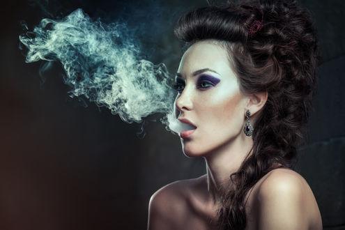 Фото Девушка с обнаженными плечами выпускает дым изо рта на фоне стены, Евгения Литовченко / Evgeniya Litovchenko